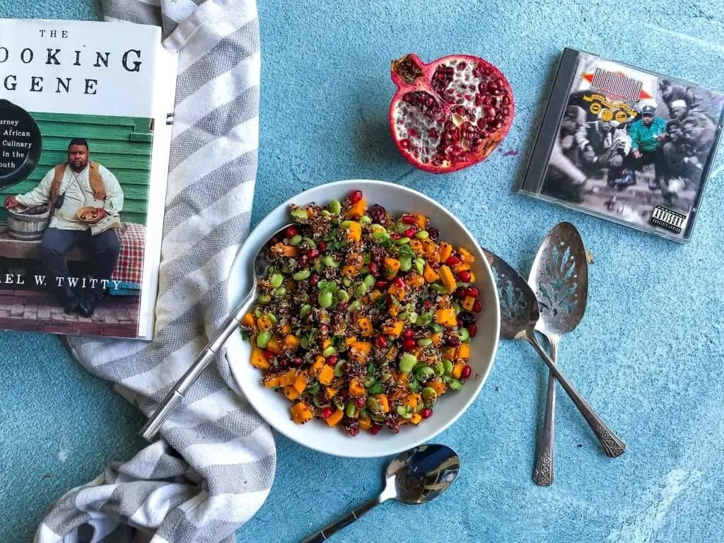 easy vegan quinoa salad with pomegrante surrounded by book and cd cover