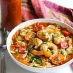 shrimp and grits in a bowl topped with red pepper sauce and cherry tomatoes