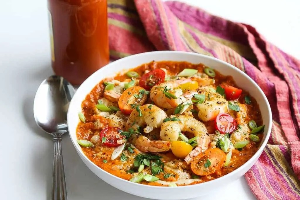 southern shrimp and grits in a bowl topped with red pepper sauce and cherry tomatoes