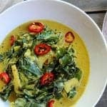 coconut curry braised collard greens in a white bowl topped with red chilis