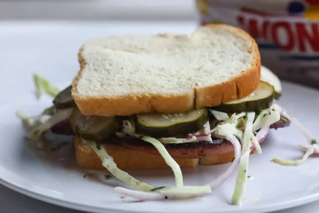 fried bolgna sandwich with slaw on white plate