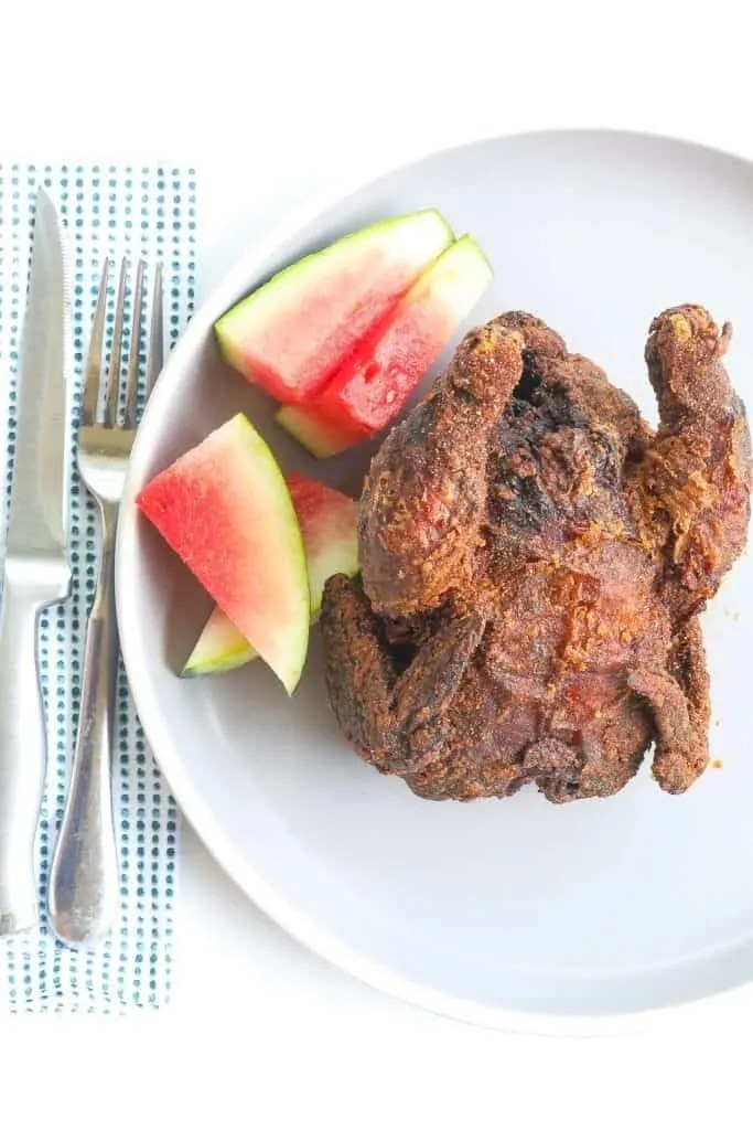 whole deep fried cornish hen on a plate with watermelon