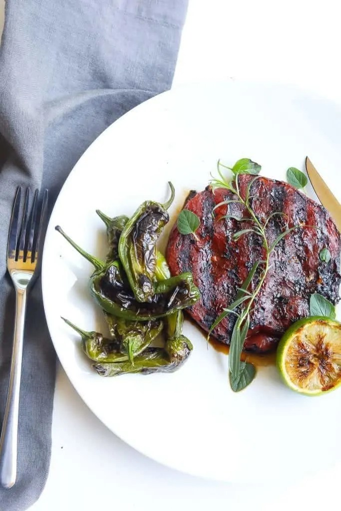 grilled watermelon on a plate with padron peppers and herbs
