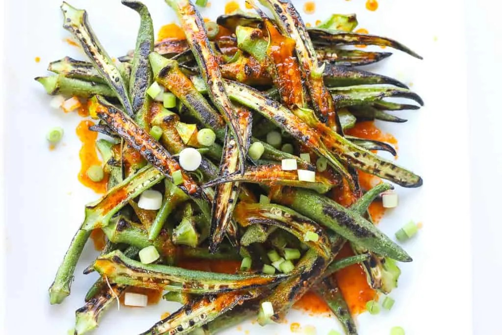 charred okra recipe topped with harissa sauce and green onions on a white plate.