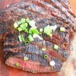 grilled flank steak sliced and topped with green onions