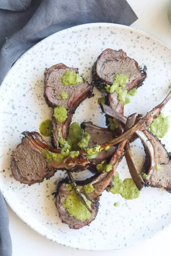 lamb chops on white plate topped with green sauce