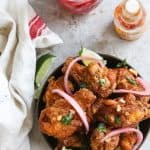brazilian fried chicken wings (frango a passarinho) in a bowl topped with red onions and cilantro