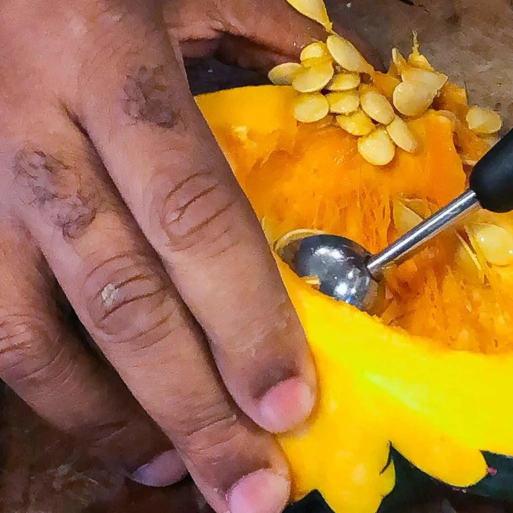 scooping seeds from acorn squash