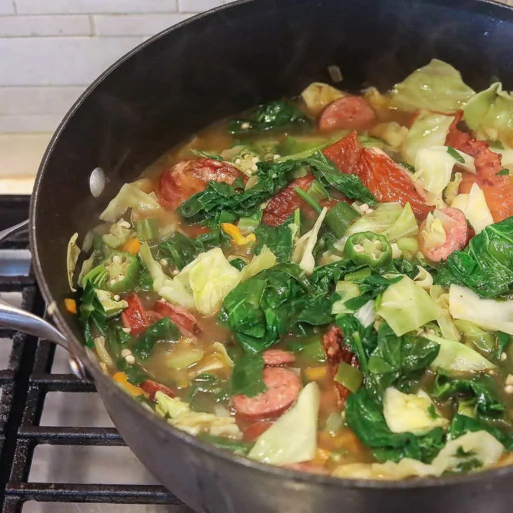 gumbo z'herbes with greens and cabbage cooking in pot