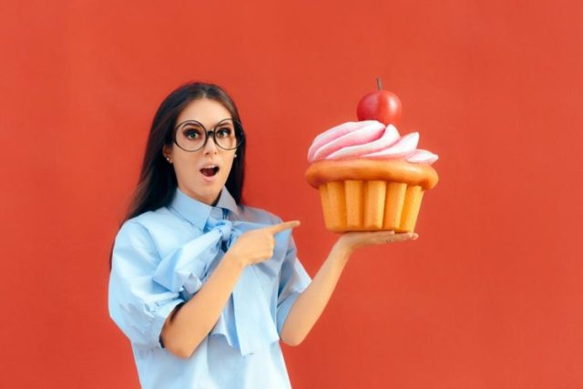Female with eyeglass holding an oversized giant cupcake on one hand in orange background, Mentrual Cycle