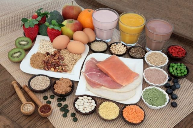 Protein foods, sliced of red meat, fish, nuts, grains, fruits, fruit and chocolate protein shakes, protein powders beautifully arranged on the table, Menstrual cycle