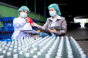 An Asian woman factory manager and staff wearing a masks, is counting stock and Check product quality of drinks, to people and Industrial plant Beverage products