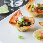 Wonton taco cup filled with seasoned black beans and topped with guacamole, pico de gallo and cilantro lime sauce