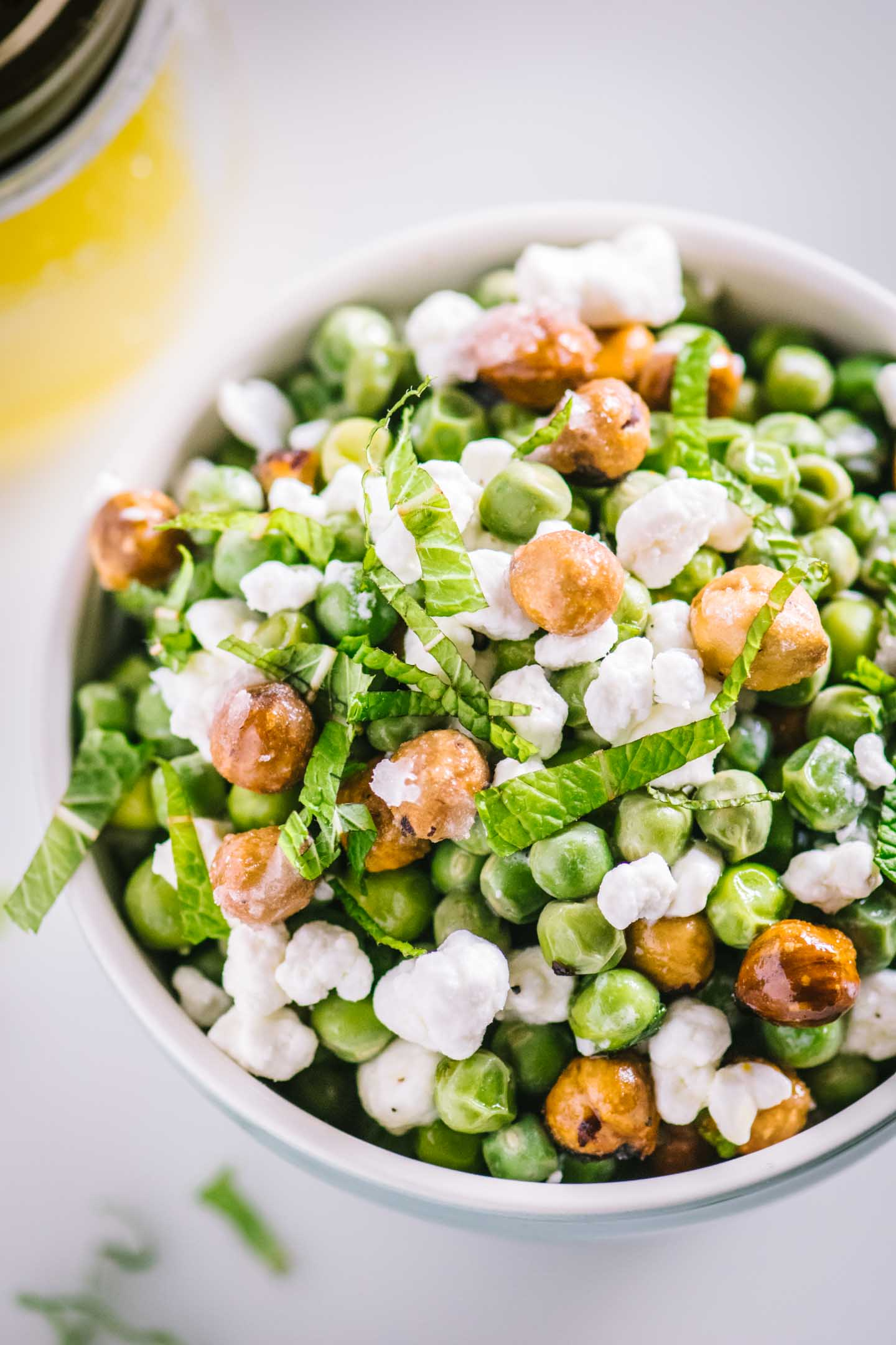 English pea salad topped with candied hazelnuts and goat cheese with a side of meyer lemon vinaigrette