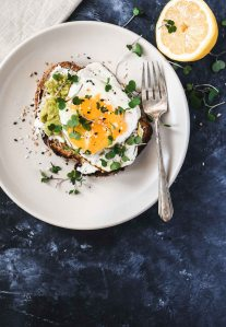 Whole grain toast topped with ricotta, avocado and a runny egg