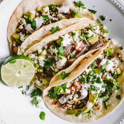 Three pork tacos topped with grilled corn salsa and cilantro lime sauce