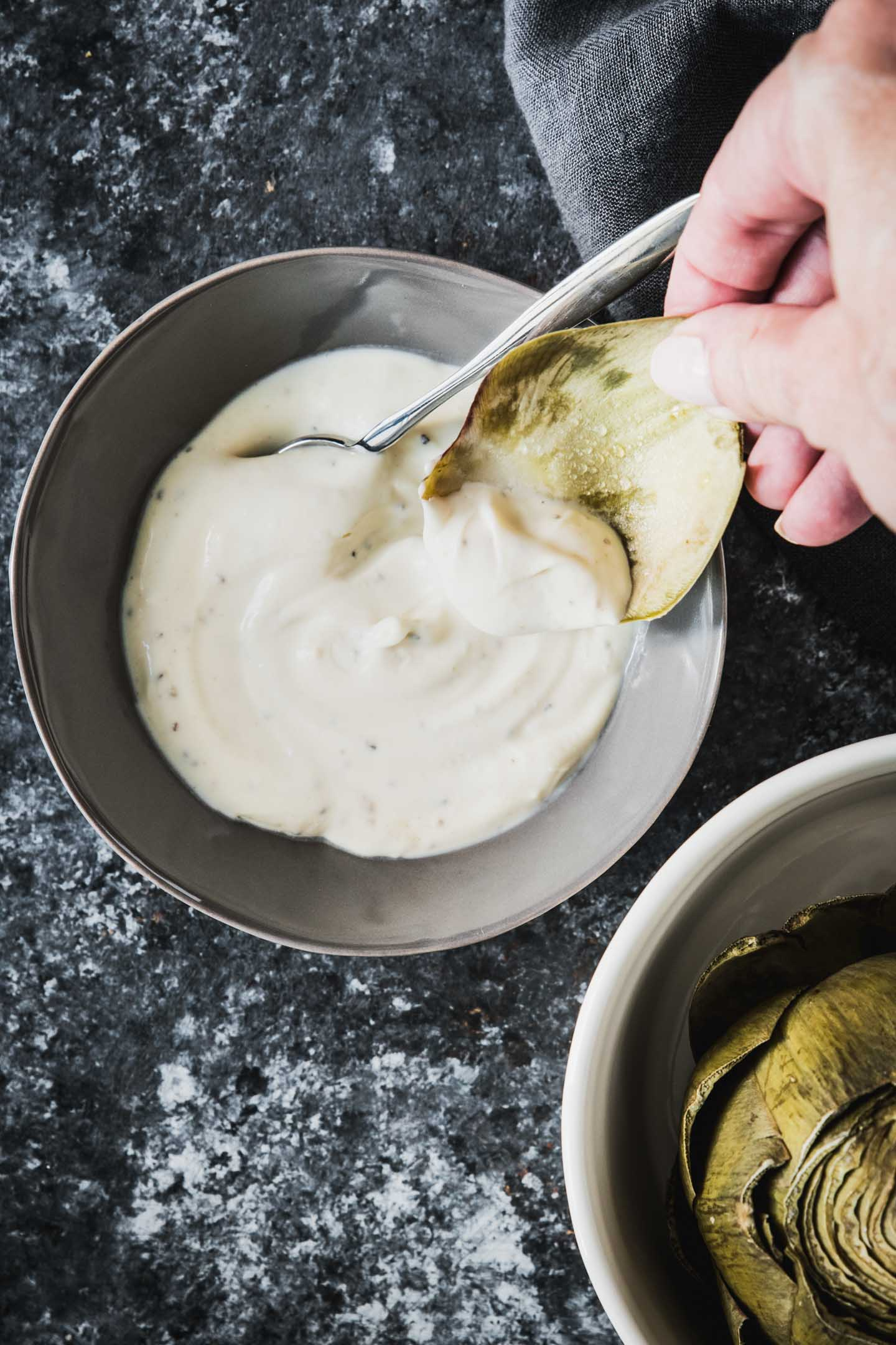 Artichoke leaf being dipped in sauce