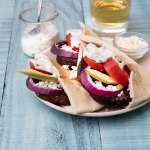 Three veggie burgers with Greek-inspired toppings