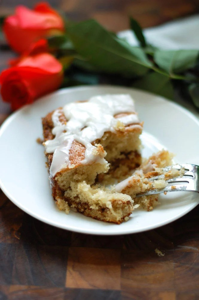 Piece of coffee cake on a white plate with roses