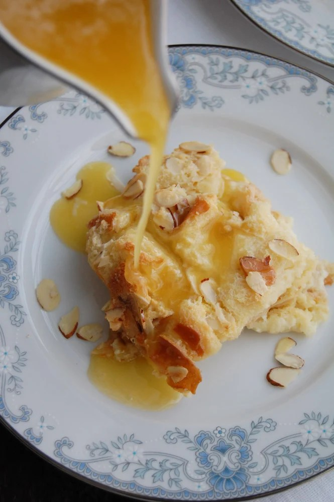 amaretto bread pudding on a plate with sauce being poured on top