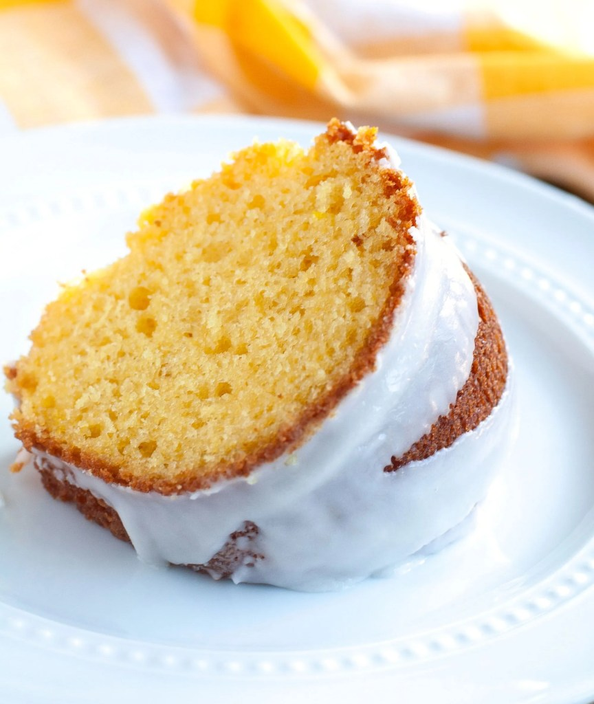 Slice of Apricot Nectar Cake on a white plate and a yellow napkin