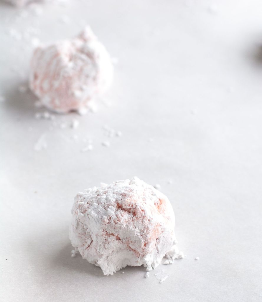 2 strawberry cookie dough balls on parchment paper