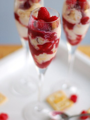 Champagne glass with ice cream and raspberries.
