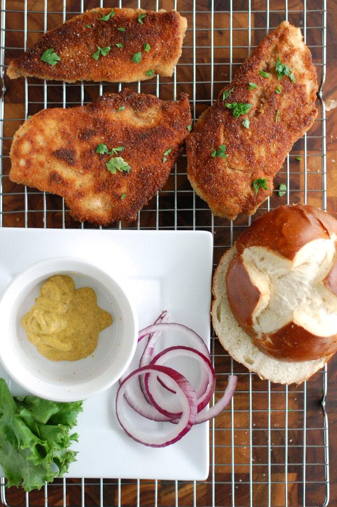 chicken schnitzel with a bowl of mustard, onion and pretzel bun