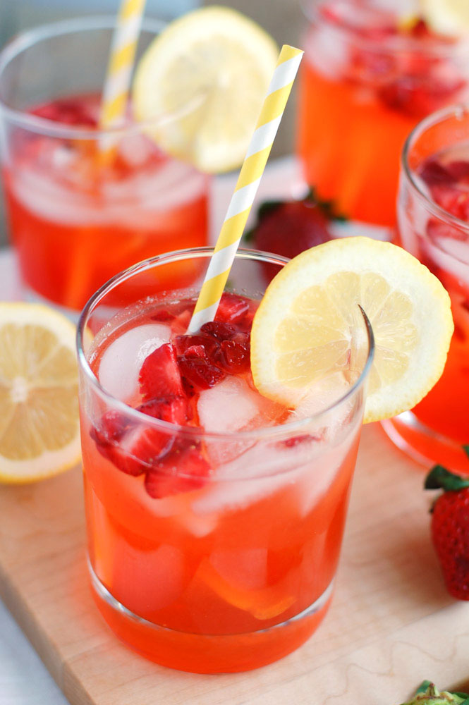 Strawberry Lemonade in a glass with yellow straw and lemon slice.