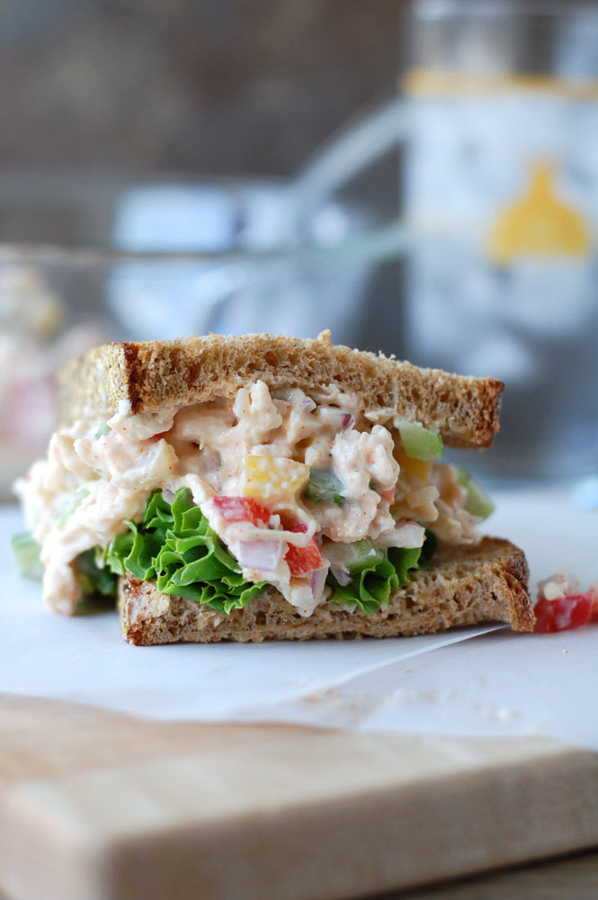 Spicy Chicken Salad Sandwiches cut in half on parchment paper