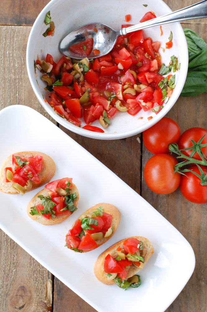 Bruschetta with olives is an AMAZING appetizer and so easy to make. A great use for garden tomatoes and basil.