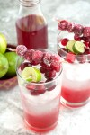 Two glasses with water, cranberries and lime wedge.