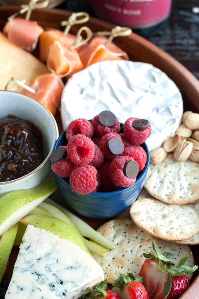 Bowl of raspberries with chocolate chips, crackers, cheese
