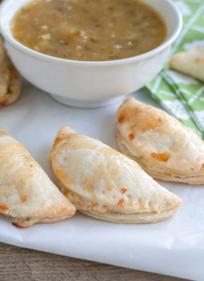salsa verde empanadas on parchment paper and a bowl of salsa verde