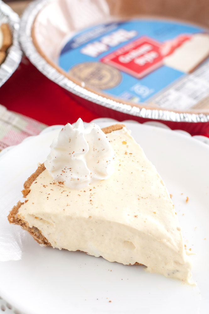 Piece of creamy pie on plate with graham cracker crust.