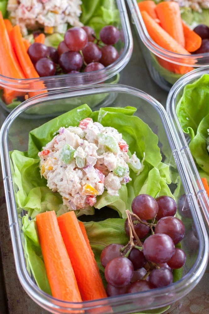 Chicken salad on a bed of lettuce, carrot sticks and grapes