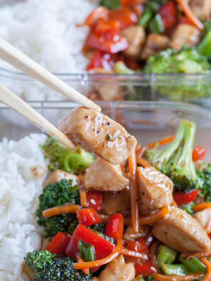 Chopsticks holding chicken with broccoli and peppers.