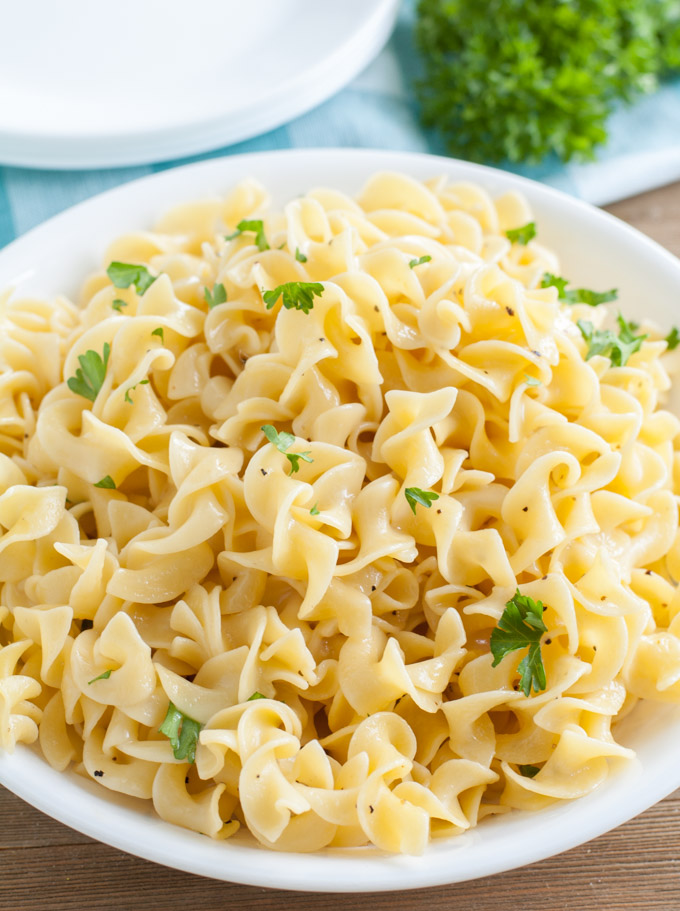 Buttered Noodles with parsley in a white bowl