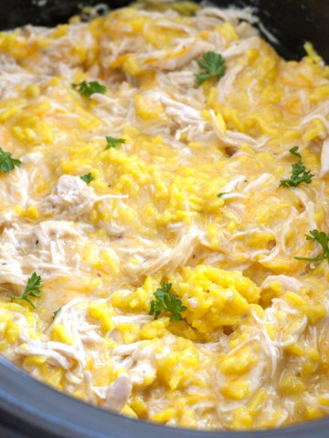 Slow cooker with shredded chicken, yellow rice and shredded cheese.