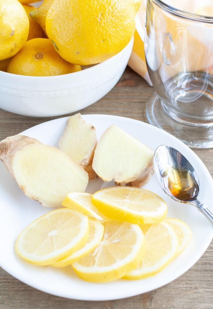 Bowl of lemons, plate of sliced lemon and ginger root
