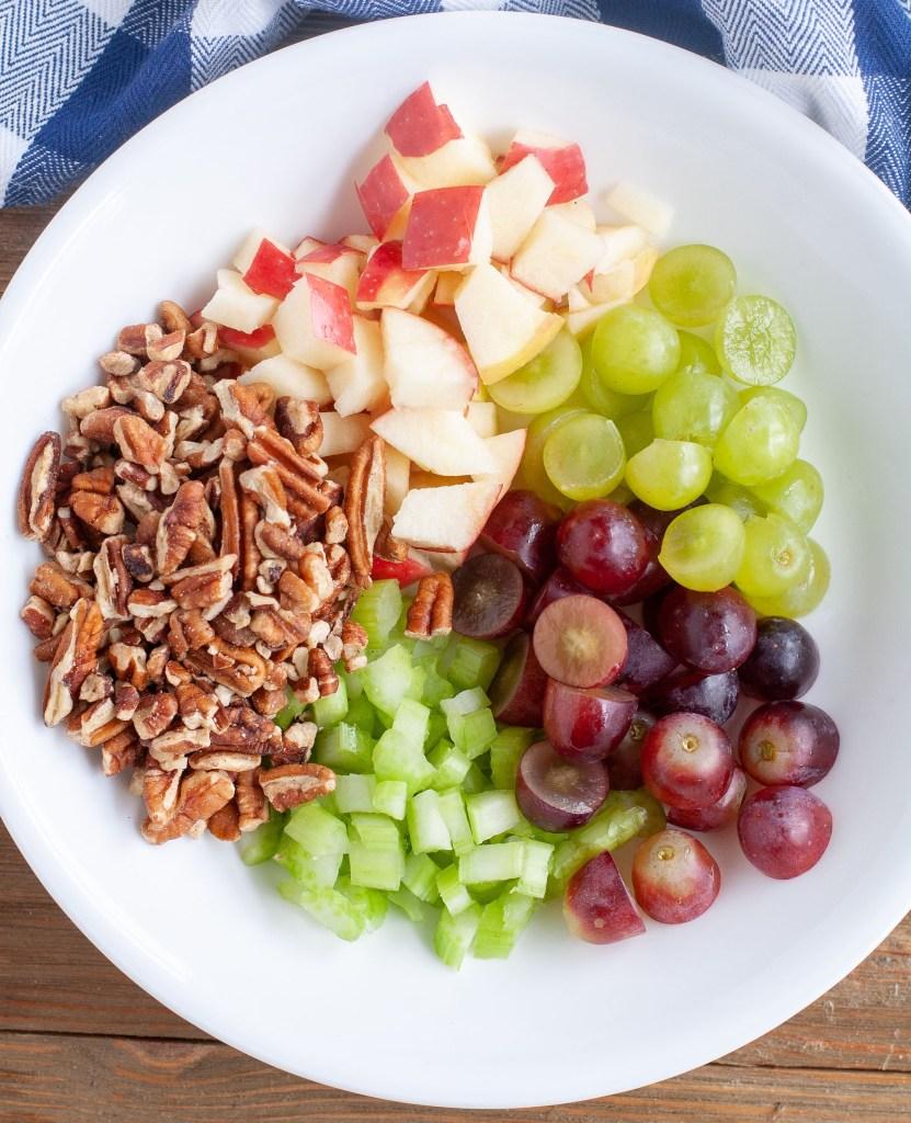 Bowl of ingredients, apples, pecans, grapes, celery.