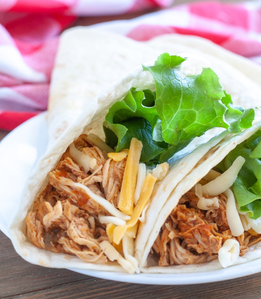 Crockpot chicken tacos in a shell on a plate