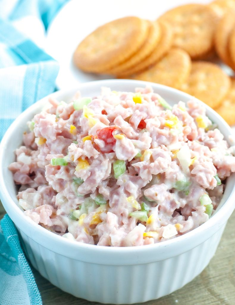 Ham salad in a white bowl with crackers in the background