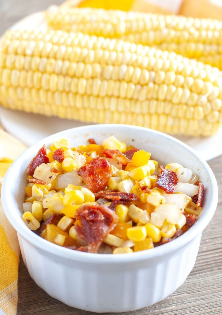 Fried corn with bacon and onions in a bowl with ears of corn in the back