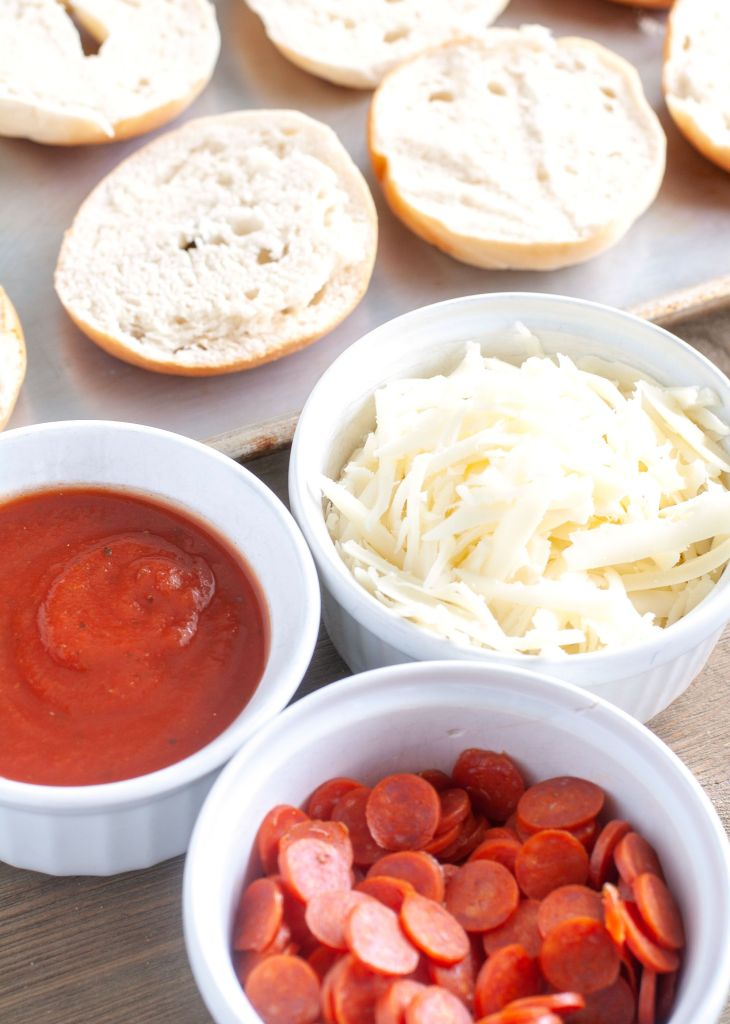 Mini bagels, bowl of sauce, bowl of shredded mozzarella cheese, bowl of mini pepperoni
