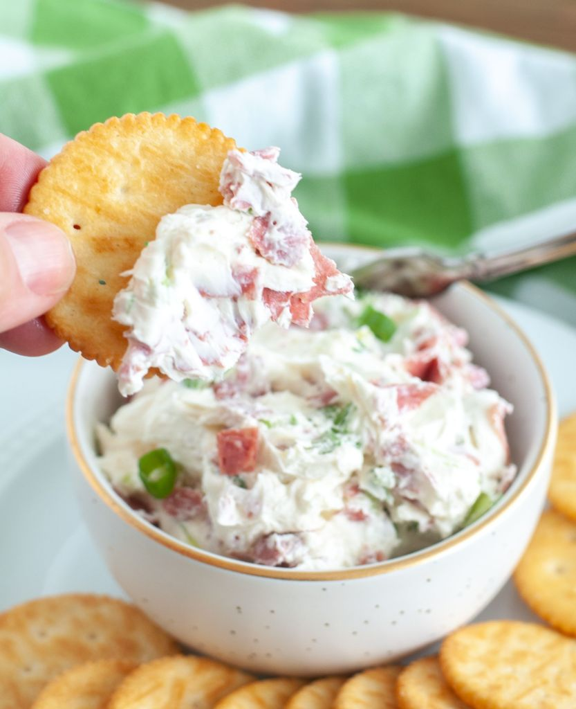 Chipped Beef Dip on a cracker being held above dip bowl