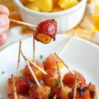Bacon wrapped pineapple on a toothpick being held above a plate