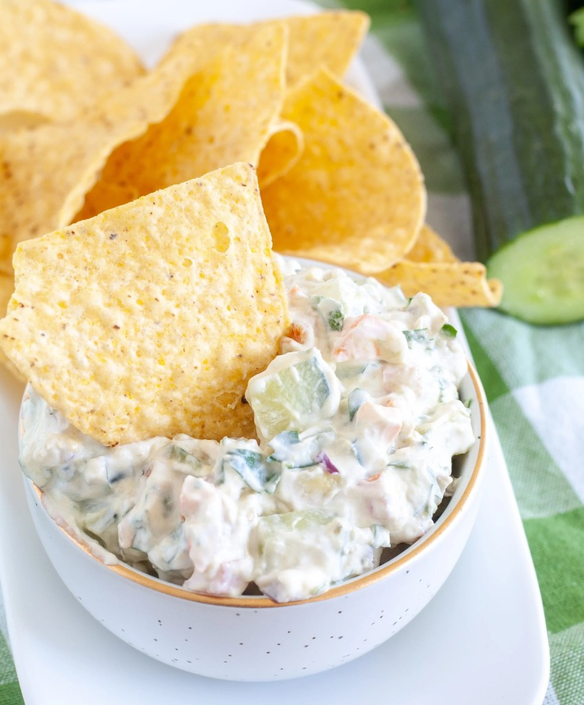 Bowl of dip with tortilla chip in it