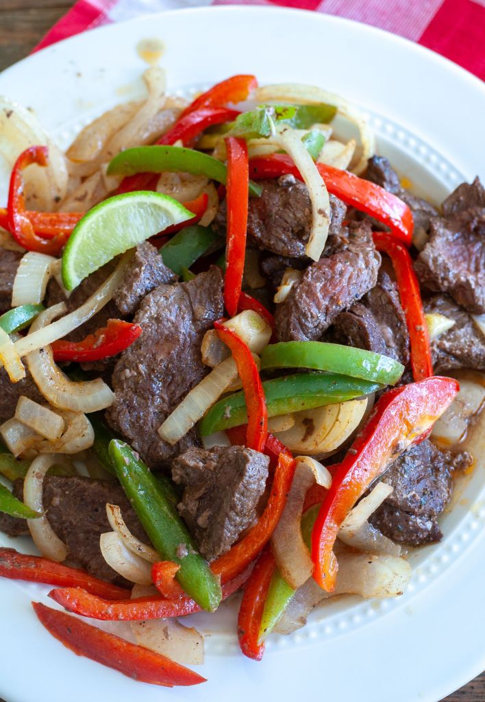 steak peppers and onions on a white plate