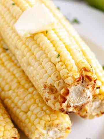 Corn stacked on a plate with pat of butter